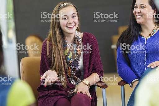 Teenage girl explaining something in a parent meeting.