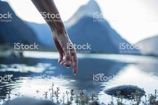 Finger touches surface of mountain lake. The landscape is reflecting on the water.